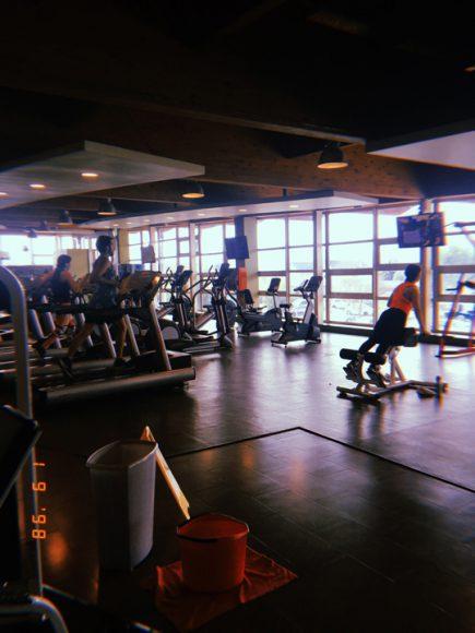 Personas haciendo ejercicio en el gym, junto con los útiles de aseo.