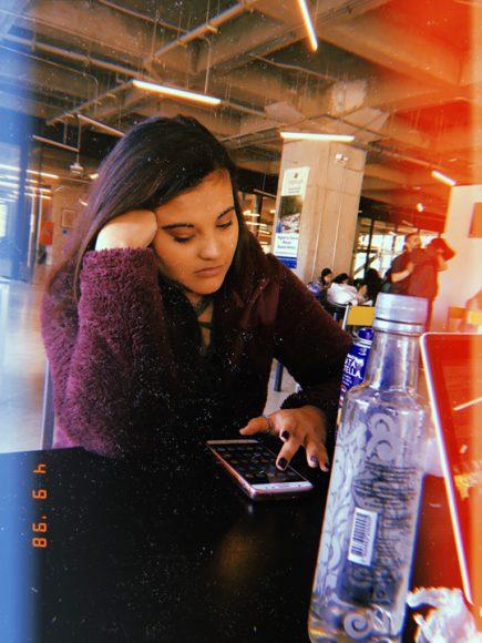 Compañera Camila reflexionando con su celular en la hora de almuerzo.