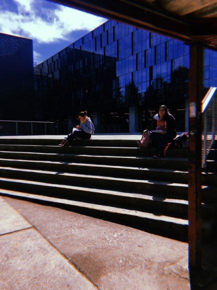 Estudiantes sentados fuera del edificio pugín una tarde soleada.