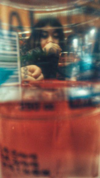 Mónica a través de un vaso con agua.